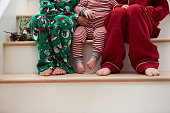 Three Children In Pajamas Sitting On Stairs At Christmas