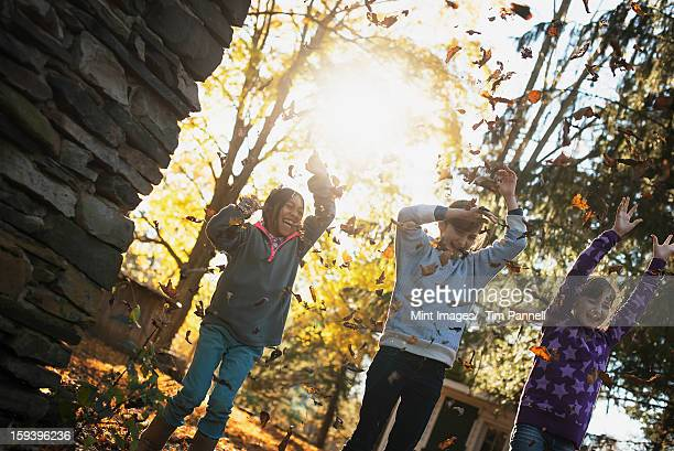 Drei Kinder im Herbst Sonne. Spielen im Freien werfen
