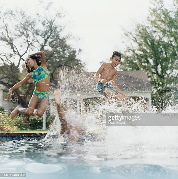 Three  children (8-10) jumping in pool, landing in water with splash
