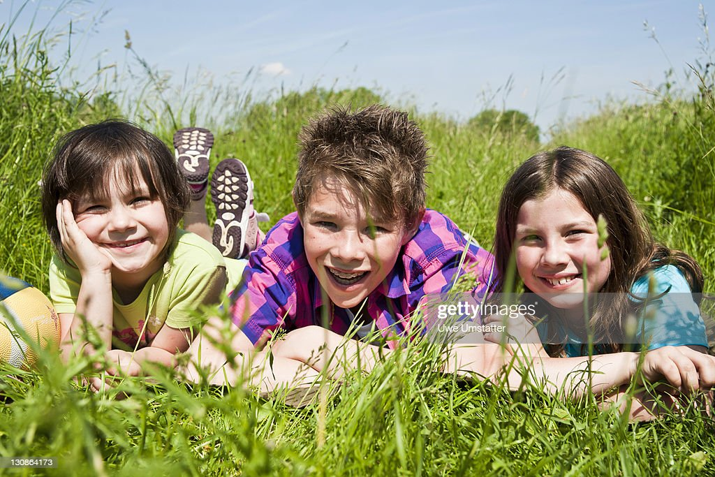 Three children lying in a meadow : Stock Photo