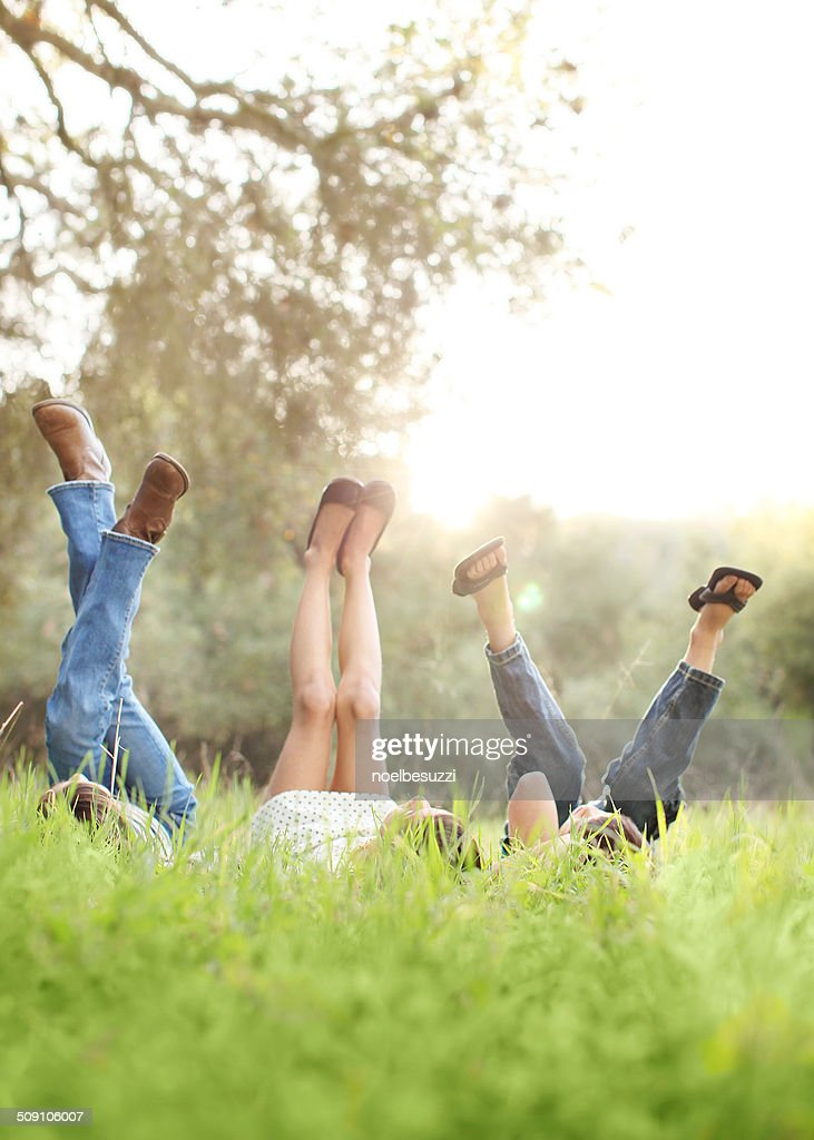 Three children lying in grass with their legs in air