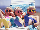 Three children lying on lounge chair at beach, portrait