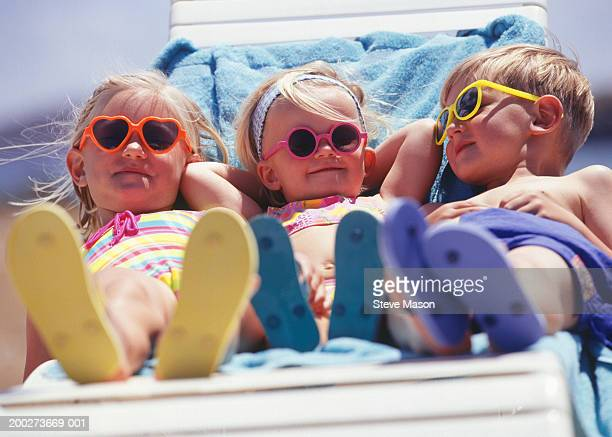 Three children (2-3), (3-4), (4-5) lying on lounge chair, surface view