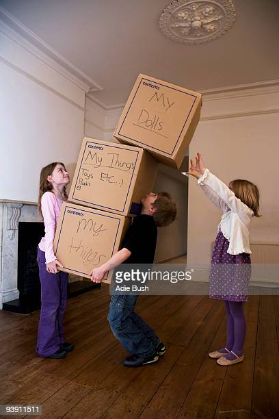 Three children moving a stack of boxes