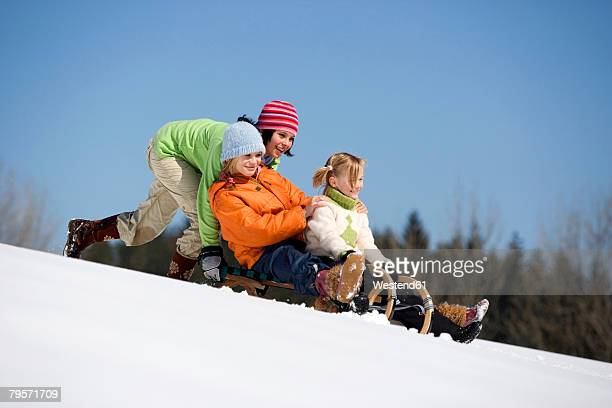 Three children on sledge