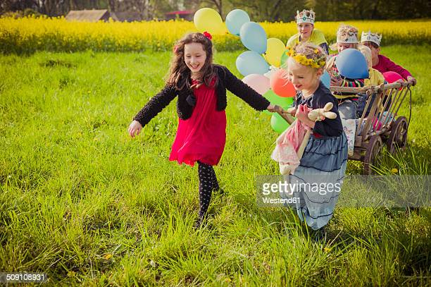 Three children on the move with wooden trolley and balloons