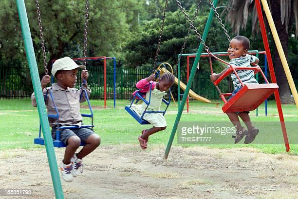 Three children on the swings