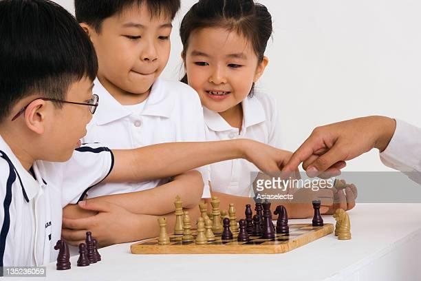Three children playing chess
