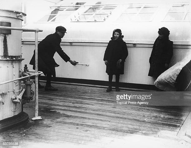 Three children playing deck quoits on board the Cunard liner Lusitania June 1912
