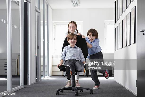 Three children playing in office corridor on office chair