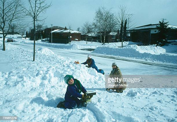 Three children playing in the snow next to a residential street