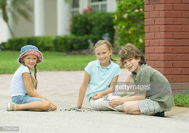 Three children playing marbles outdoors