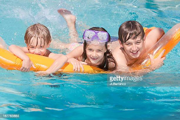 Three Children Playing on a Float in the Swimming Pool