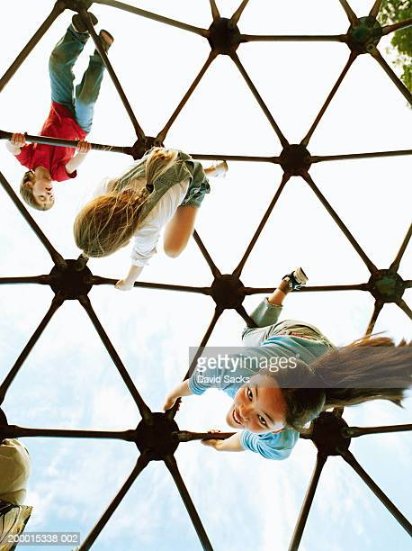Three children (4-13) playing on climbing dome, low angle view