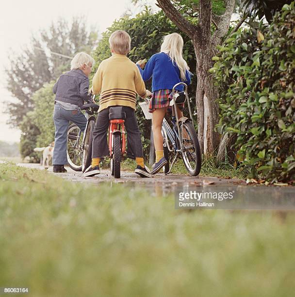 Three children riding bicycles on sidewalk