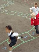 Three children (6-8) running in playground (blurred motion)