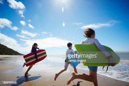Three children running into the ocean