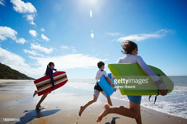 Three children running into the ocean