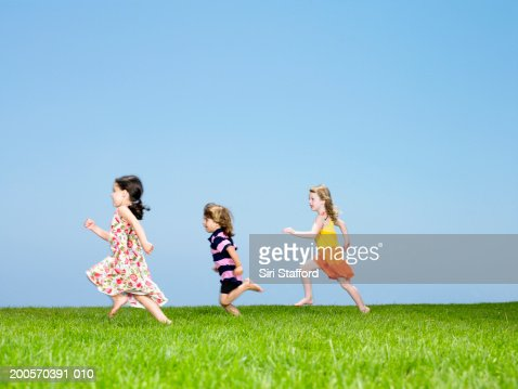 Three children (3-4) running on lawn, side view : Stock Photo