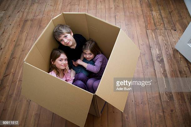 Three children sitting inside a box.