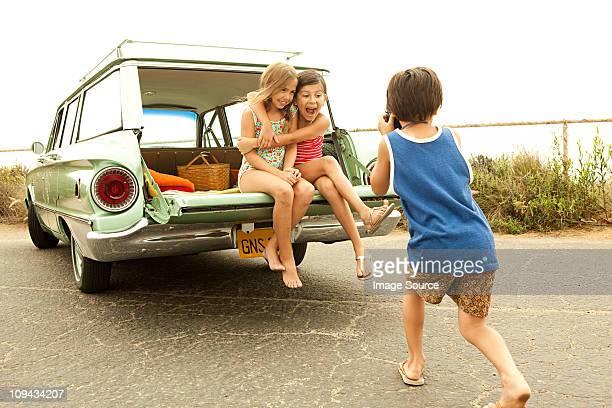 Trois enfants assis sur le dos de estate voiture en prenant des photographies