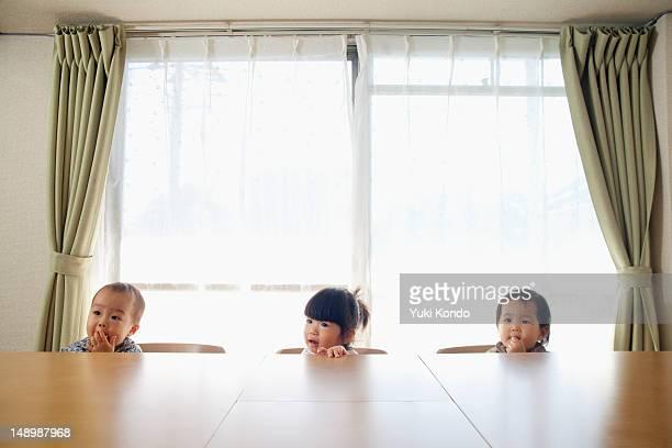 Three children sitting on the chair.