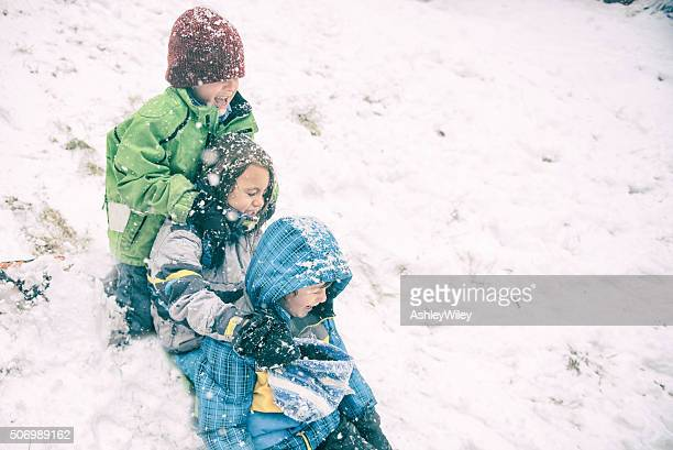 Three children sled during a snow storm