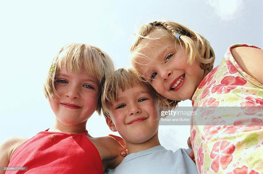 Three children (3-6) smiling, portrait, low angle view : Stock Photo