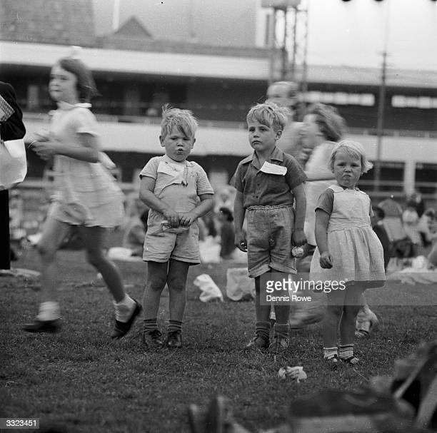 Three children stand frozen in time as others run past in a blur They are attending a party for sick and needy children at Sydney Cricket Ground...