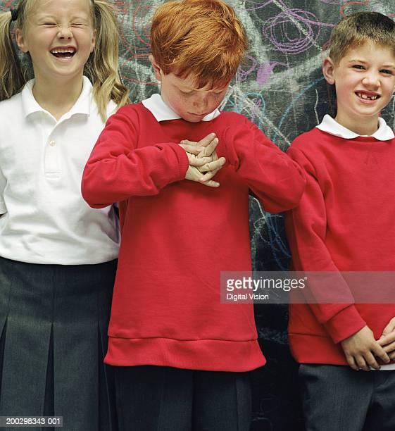 Three children (6-8) standing by blackboard, boy clasping hands