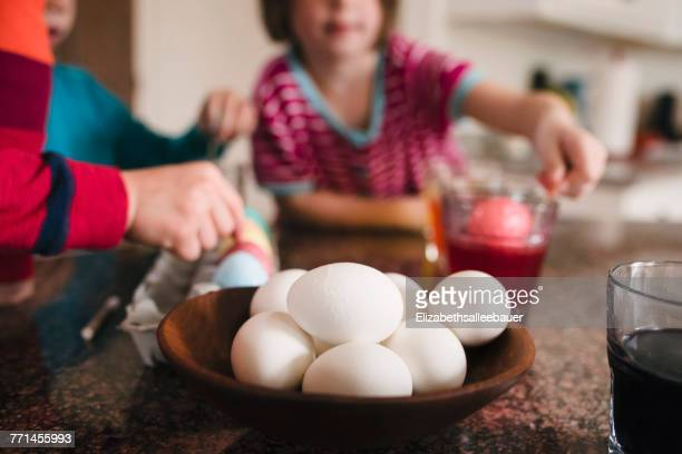 Three children standing in the kitchen dying Easter eggs
