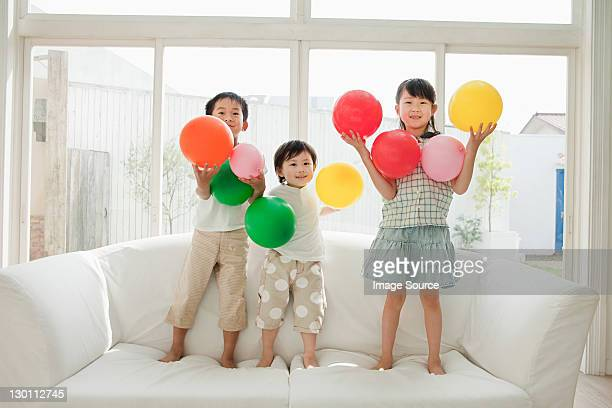 Three children standing on sofa with balloons