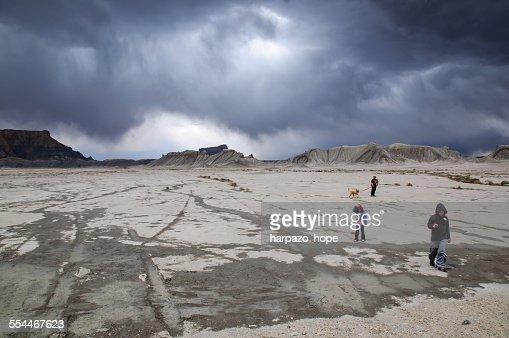 Three children walking through the desert.