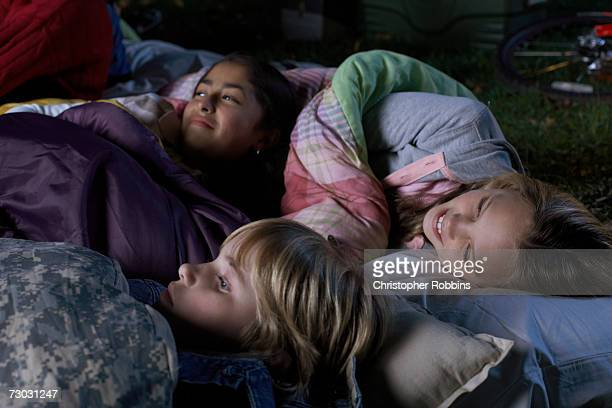 Three children (8-9, 10-11, 12-13) watching film in garden at night, close-up