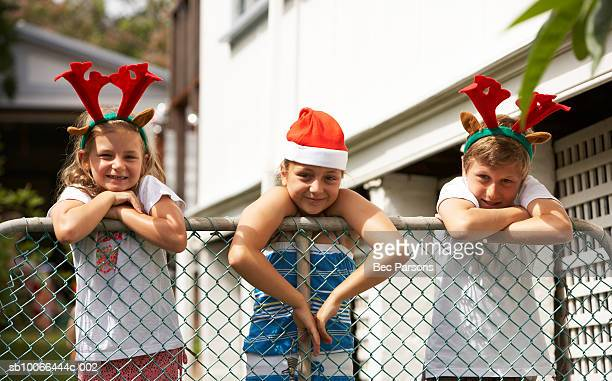 Three children (7-12) wearing Christmas hats at fence
