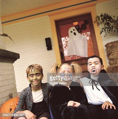 Three children (5-9) wearing Halloween costumes, portrait : Stock Photo