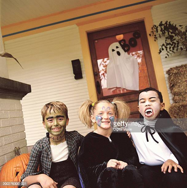 Three children (5-9) wearing Halloween costumes, portrait