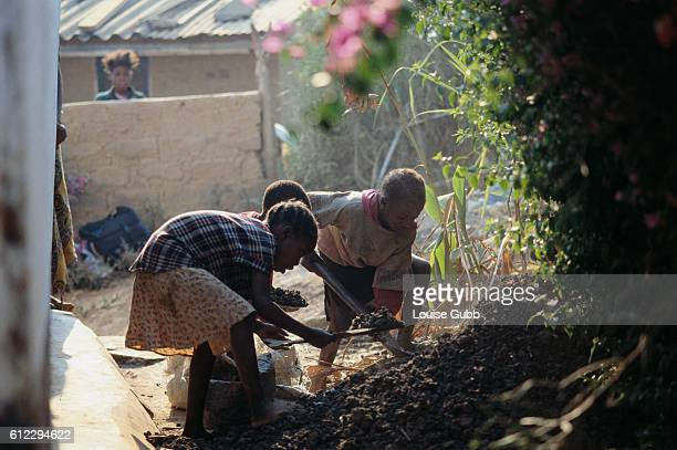 Three children work in their yard to bag manure they collected at Kitwe Sewerage Plant The treated human waste can be used as fertilizer in vegetable...