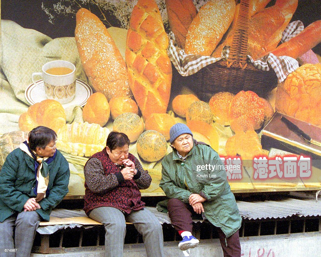 Three Chinese women take a break outside a bakery shop with a billboard featuring bread and cake December 2 2001 in Beijing China After China's entry...
