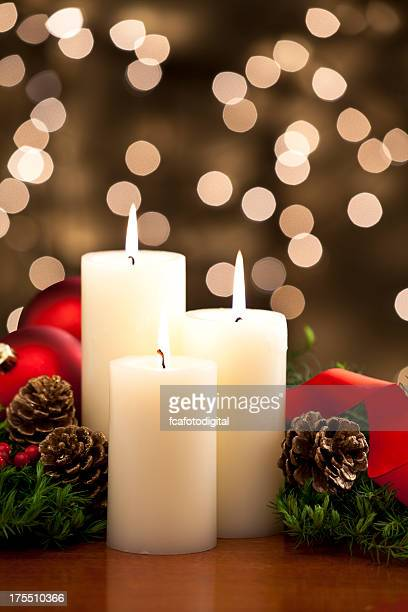 Three christmas candles with defocused lights on background