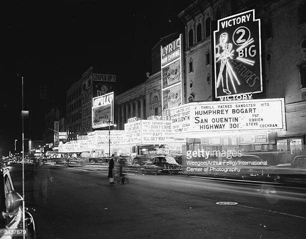 Three cinemas in TImes Square New York City the Victory the Lyric and the Apollo with their brightlylit signs The Victory is showing two gangster...