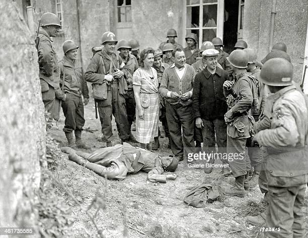 Three civilians including a woman talk with US troops June 1944 A dead German soldier is at their feet June 1944 At left is a doctor of Engineer...