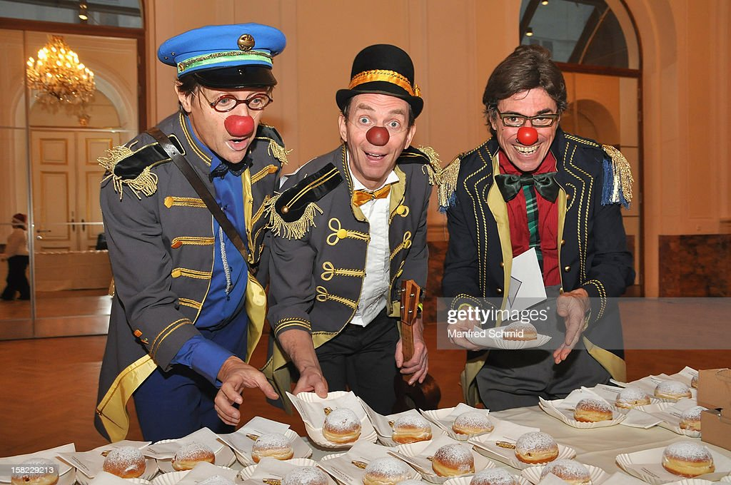Three clowns looking for doughnuts at the Christmas ball for children Energy For Life - Heat For Children's Hearts at Hofburg Vienna on December 11, 2012 in Vienna, Austria.