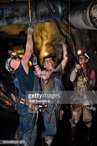 Three coal miners installing ventilation tube in mine, clsoe-up