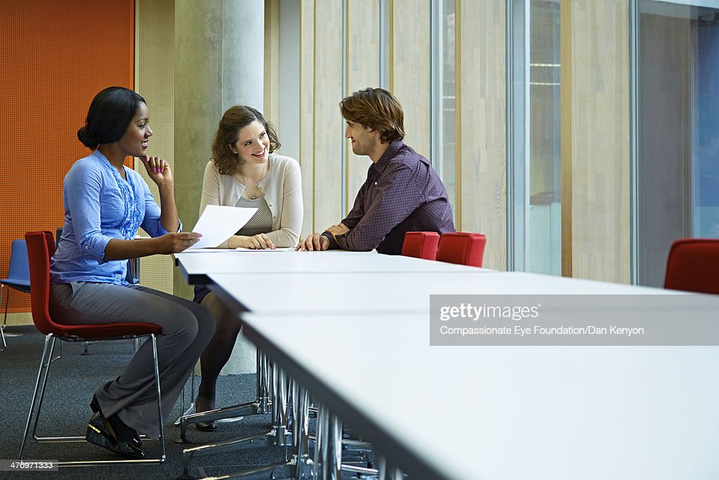 Three colleagues discussing in meeting room : Stock Photo