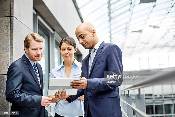 Three colleagues discussing work on a tablet