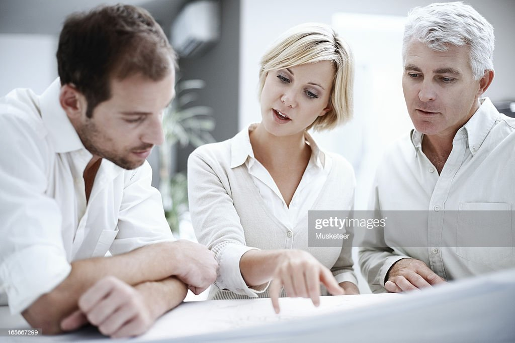 Three colleagues solving a problem : Stock Photo