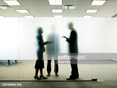 Three colleagues standing behind frosted glass in office, talking : Stock Photo