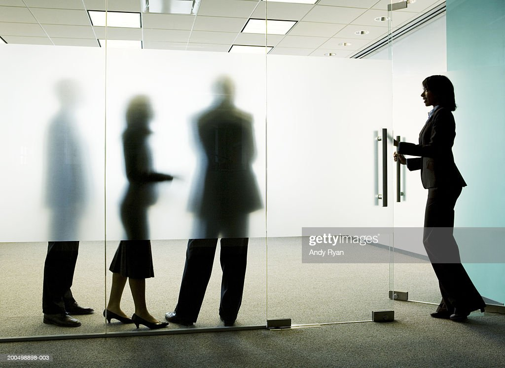 Three colleagues standing behind frosted glass, woman entering office : Stock Photo