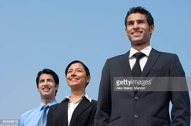 three colleagues standing, smiling